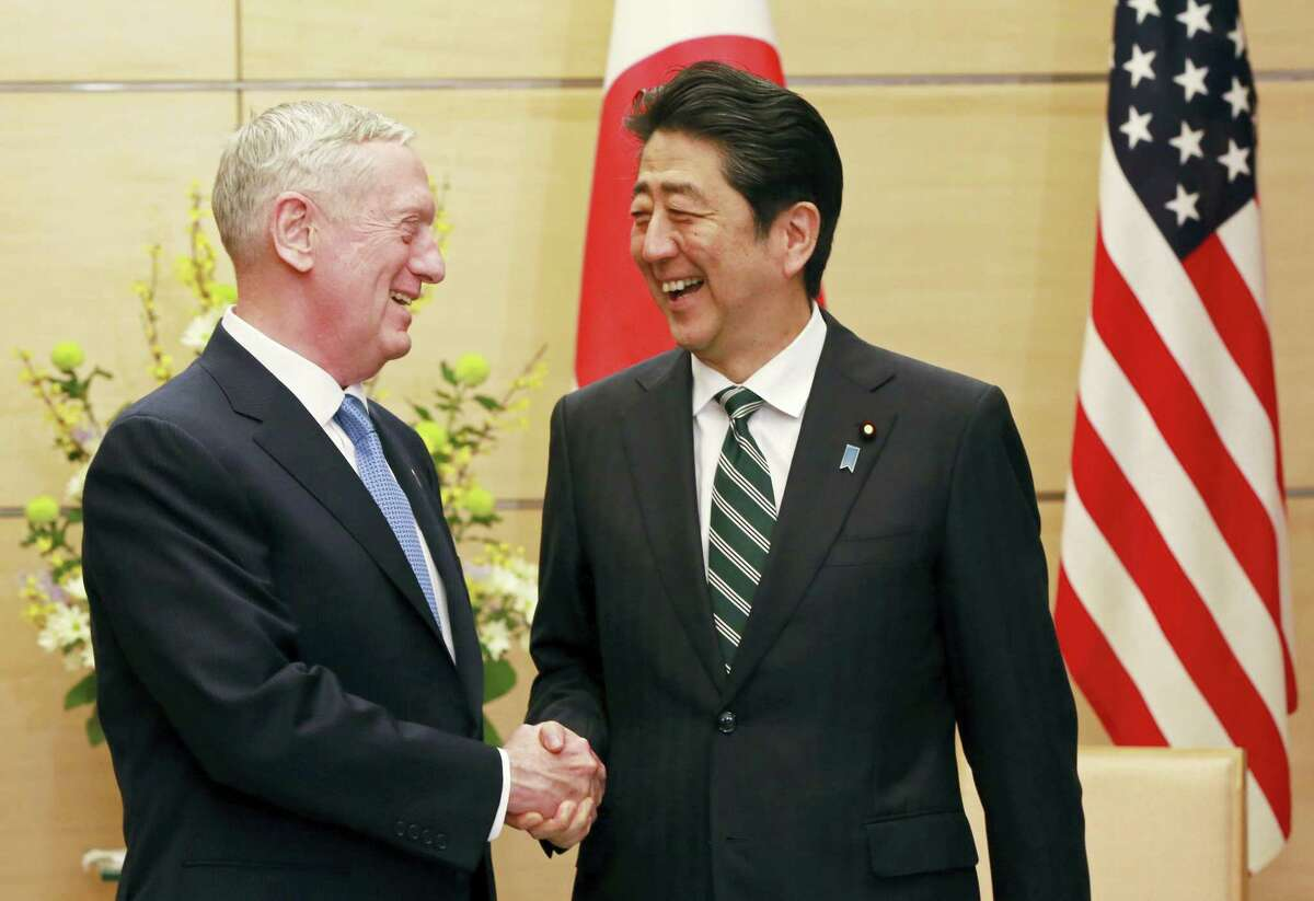 """U.S. Defense Secretary Jim Mattis, left, and Japanese Prime Minister Shinzo Abe, right, shake hands at the prime minister's office in Tokyo, Friday, Feb. 3, 2017. In an explicit warning to North Korea, U.S. Defense Secretary Mattis on Friday said any use of nuclear weapons by the North on the United States or its allies would be met with what he called an """"effective and overwhelming"""" response."""