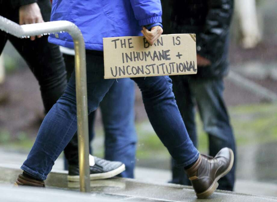 "A person walks away from the federal courthouse in Seattle carrying a sign that reads ""The Ban is Inhumane and Unconstitutional,"" Friday, Feb. 3, 2017, following a hearing in federal court in Seattle. Photo: Ted S. Warren — AP Photo / Copyright 2017 The Associated Press. All rights reserved."