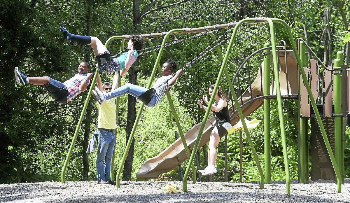 (Arnold Gold/Hearst Connecticut Media) People take advantage of a swing set during the GRO1000 dedication ceremony for Cherry Ann Park in New Haven on 6/10/2017. The Scotts Miracle-Gro Foundation donated $40,000 for the park.
