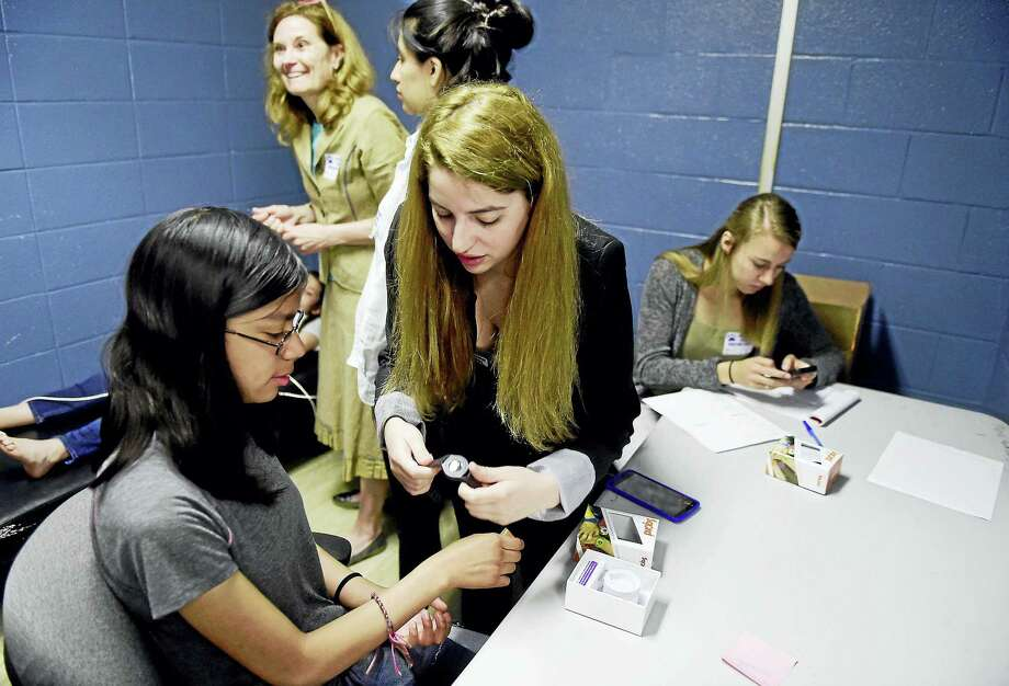Sabrina Svozzi, a University of New Haven nutrition and dietetics major, fits a Sqord waterproof fitness activity tracker onto fifth-grader Danyela Lanche-Flores, 11. At rear, from left, are UNH assistant professor Anne Davis of the nutrition and dietetics department and her students Stephanie Alvarez, 22 and Riley Knebes, far right. Photo: Peter Hvizdak/Hearst Connecticut Media   / Peter Hvizdak