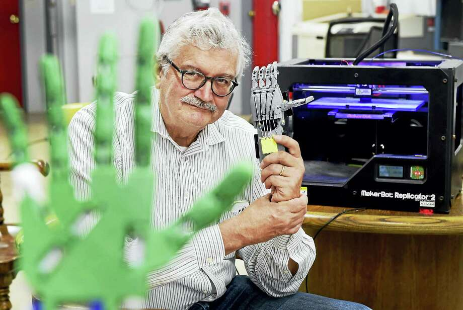 Using a 3D printer, Bruce O'Donnell, 66, of Cheshire is framed by a robotic hand and arm prosthetic prototype, left, and holds a functional mechanical prosthetic, made at MakeHaven in New Haven. Photo: Peter Hvizdak — HEARST CONNECTICUT MEDIA   / Peter Hvizdak
