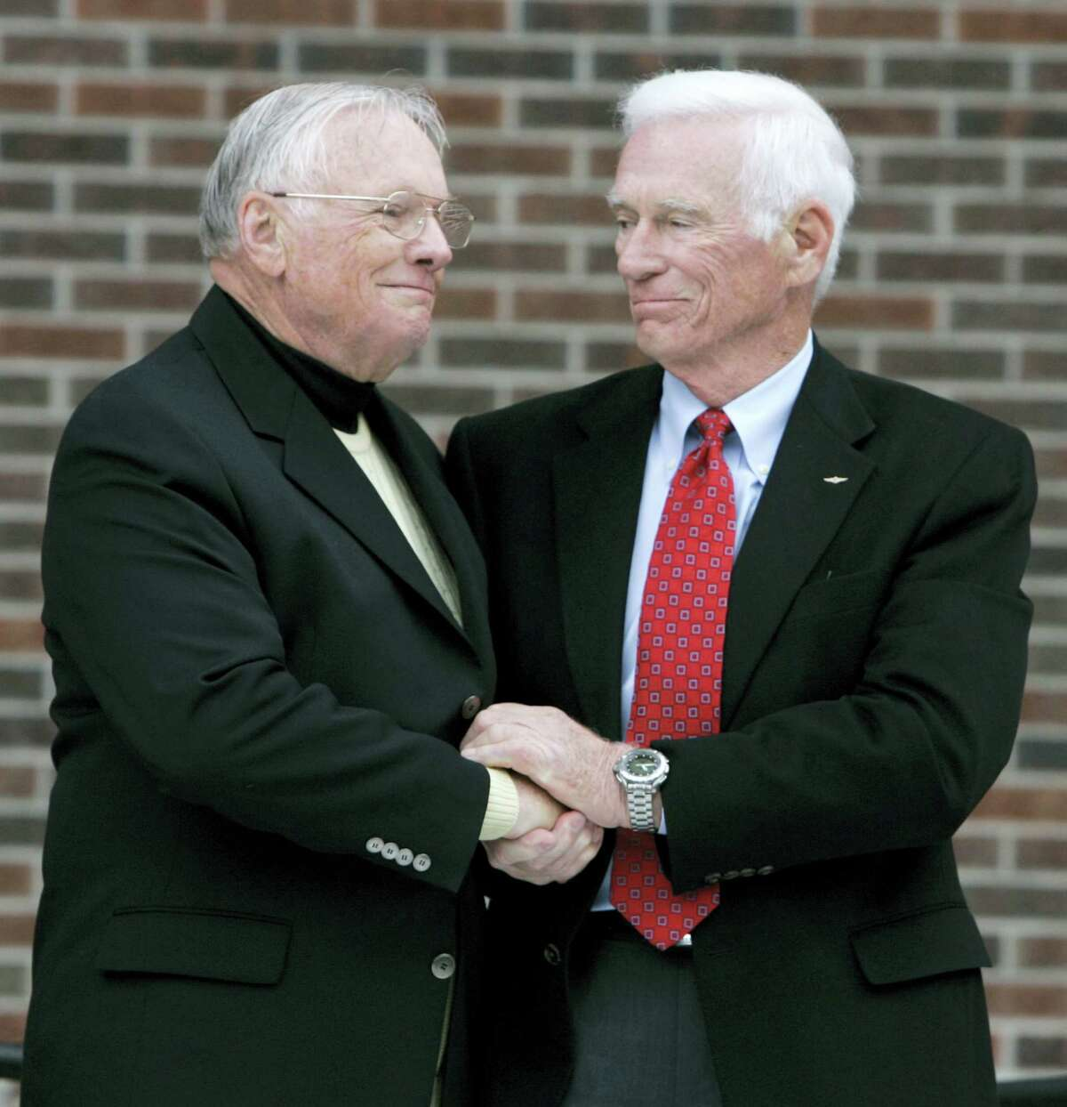 FILE - In a Oct. 27, 2007 file photo, former astronaut Neil Armstrong, left, is congratulated by fellow ex-astronaut Gene Cernan following the dedication ceremony of the Neil Armstrong Hall of Engineering at Purdue University in West Lafayette, Ind. NASA announced that former astronaut Gene Cernan, the last man to walk on the moon, died Monday, Jan. 16, 2017, surrounded by his family. He was 82.