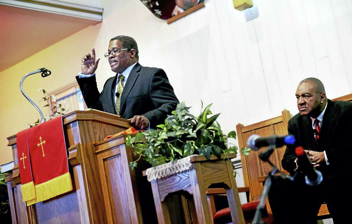 Minister Bruce Goldson, left, gives the keynote speech at the annual celebration of the legacy of the Rev. Martin Luther King Jr. at Macedonia Baptist Church in Ansonia Monday. At right is the Rev. Alfred L. Smith Jr.