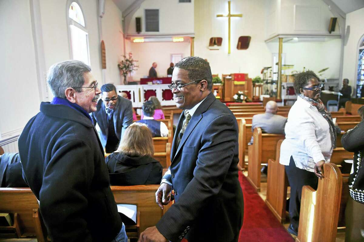 Robert Amaro of Beacon Falls, left, speaks with Minister Bruce Goldson, center, before the annual Martin Luther King Jr. celebration at Macedonia Baptist Church in Ansonia Monday.