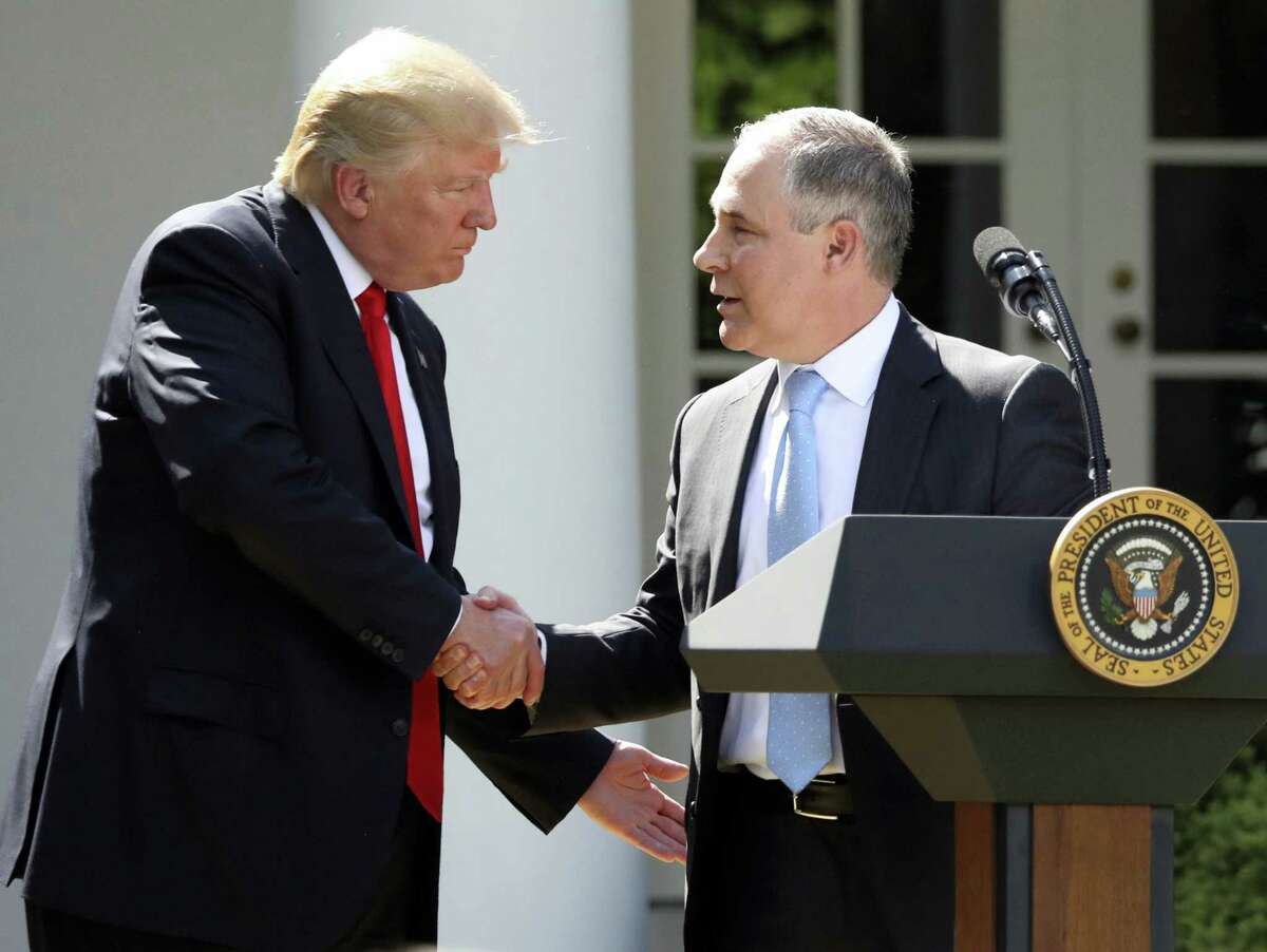 In this June 1, 2017 file photo, President Donald Trump shakes hands with EPA Administrator Scott Pruitt after speaking about the US role in the Paris climate change accord in the Rose Garden of the White House in Washington. Trump's recent decision to pull the United States from the international climate deal reached in Paris was but the latest in a rapid-fire series of moves that would weaken or dismantle federal initiatives to reduce carbon emissions, which scientists say are heating the planet to levels that could have disastrous consequences.