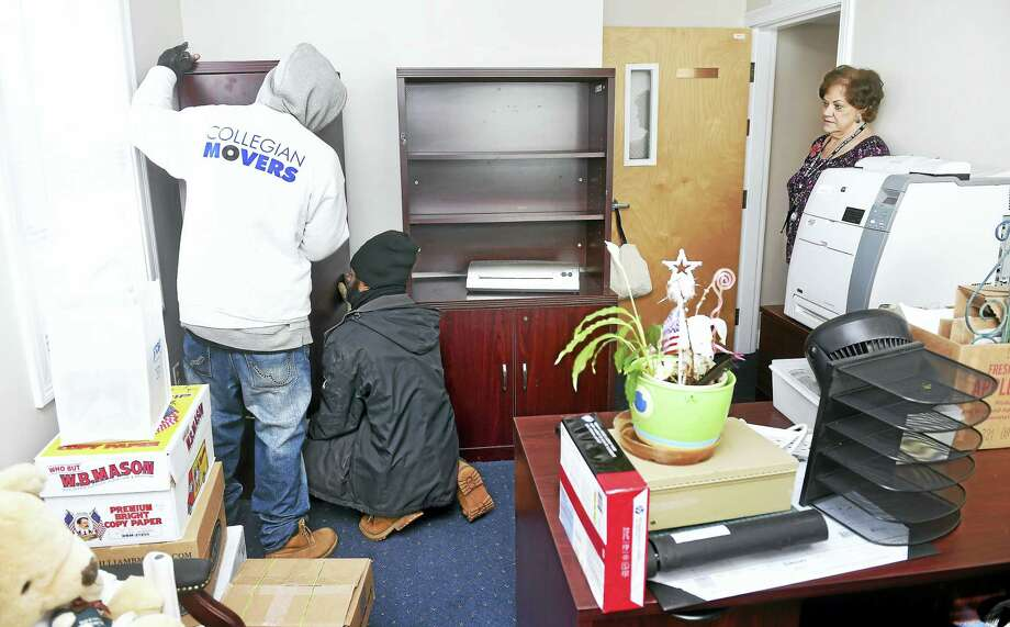 From left, Jerrod Preston and Kishon Phillip of Collegian Movers move furniture into the interim office of Maureen Piccolo, lead administrative assistant at Boys & Girls Village, on the Crown Corporate Park campus in Milford. Photo: Arnold Gold — New Haven Register