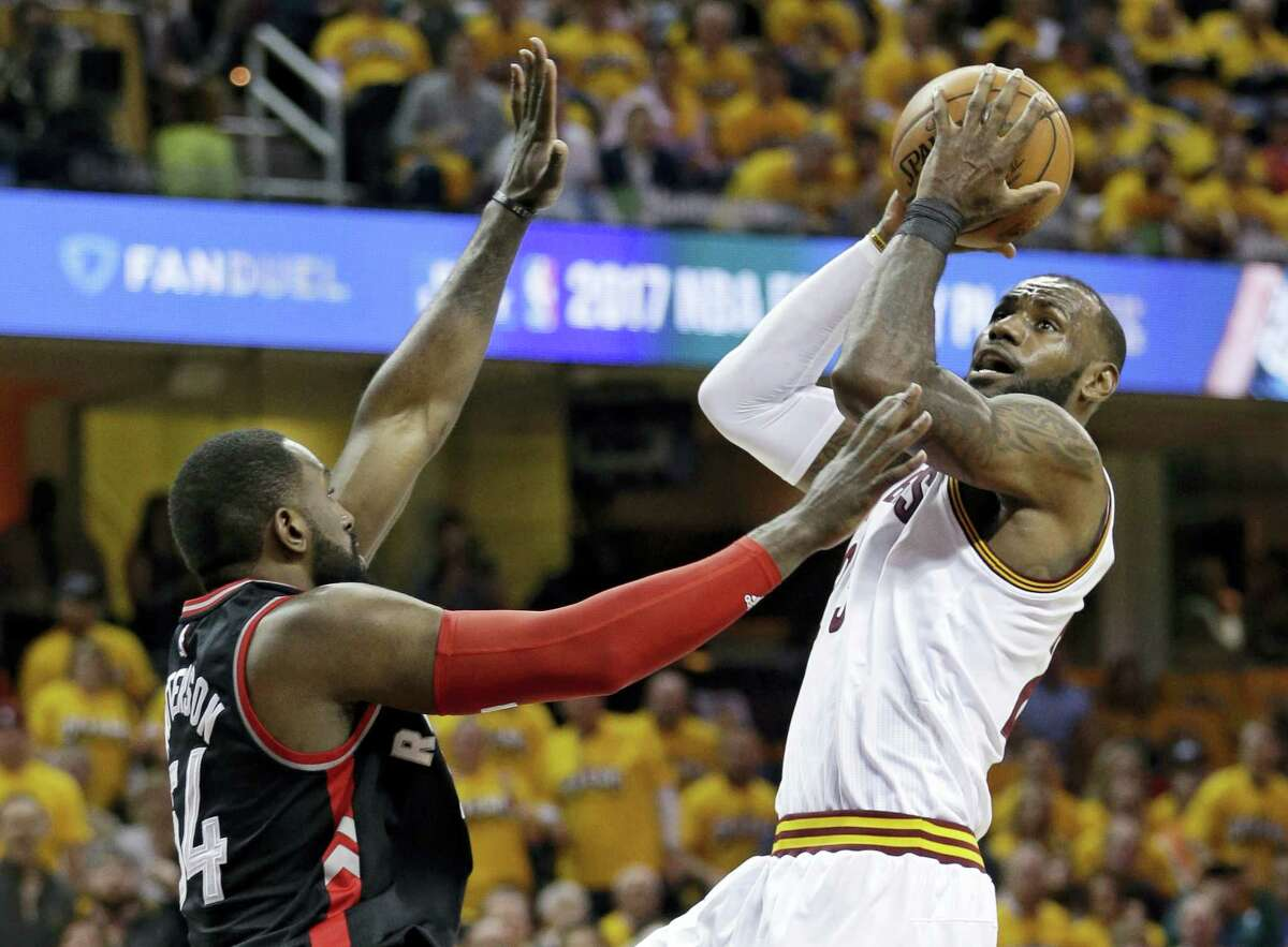 The Cavaliers' LeBron James, right, drives to the basket against the Raptors on Monday.