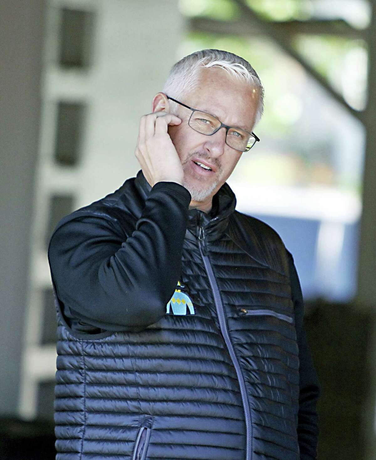 Trainer Todd Pletcher watches activities outside his barn at Churchill Downs.