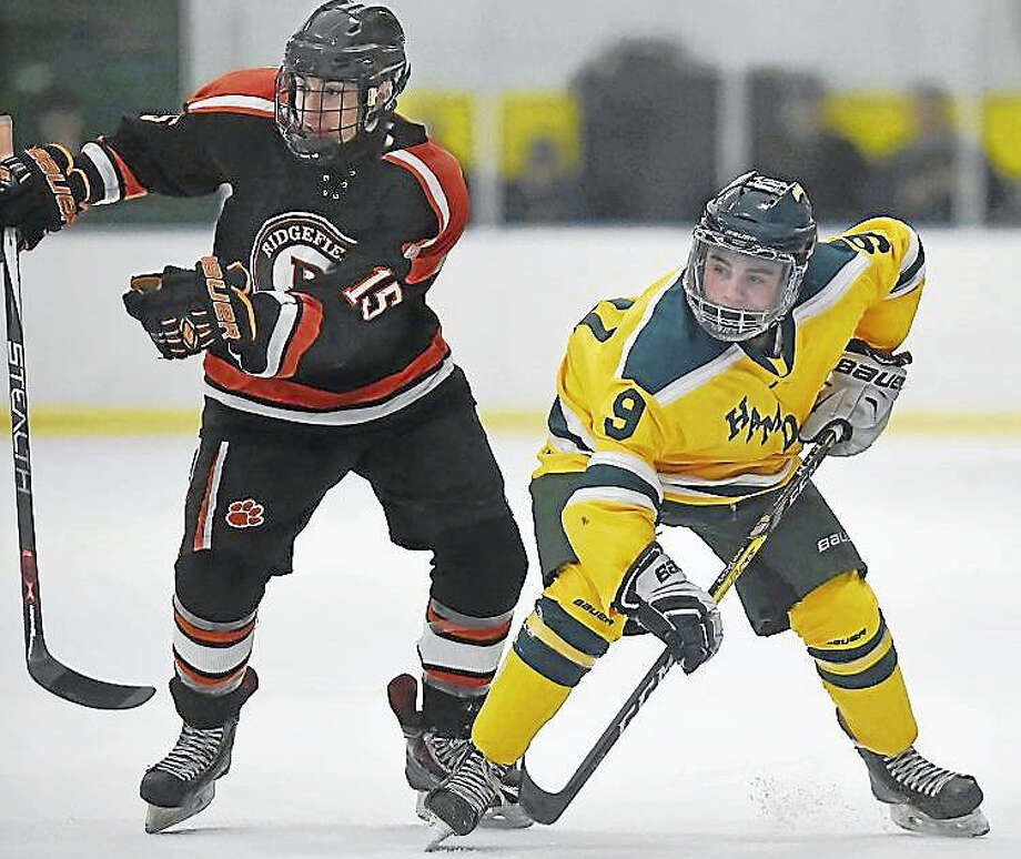 Hamden sophomore forward Eddy Fracasso battles Ridgefield senior center Joe Signorelli in a faceoff Thursday in a 2-1 loss for the sixth-ranked Green Dragons to No. 1 Ridgefield at Astorino Rink in Hamden. Photo: Catherine Avalone — New Haven Register