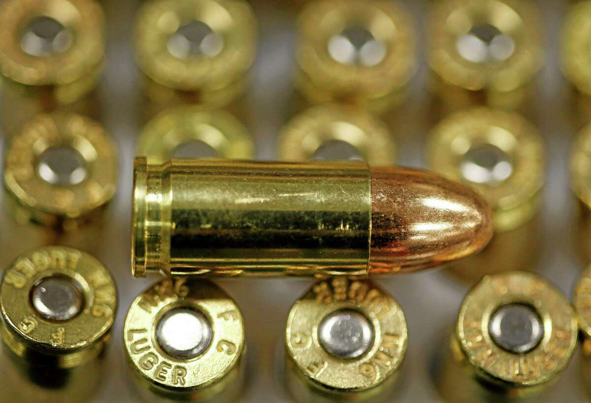 A 9 mm bullet rests on top of others in a box on the counter at Duke's Sport Shop in New Castle, Pa., in 2013.