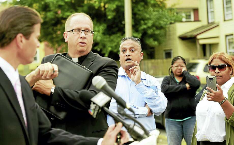 Fazlay Rabbi, co-owner of Slyce Pizza & Bar restaurant, third from left, attempts to ask a question and is later rebuffed by the Rev. James Manship, second from left, as Hamden Police Chief Thomas Wydra, far left, speaks during a press conference in 2016 to denounce violence near the retaurant. Photo: Peter Hvizdak — New Haven Register File Photo   / ?2016 Peter Hvizdak