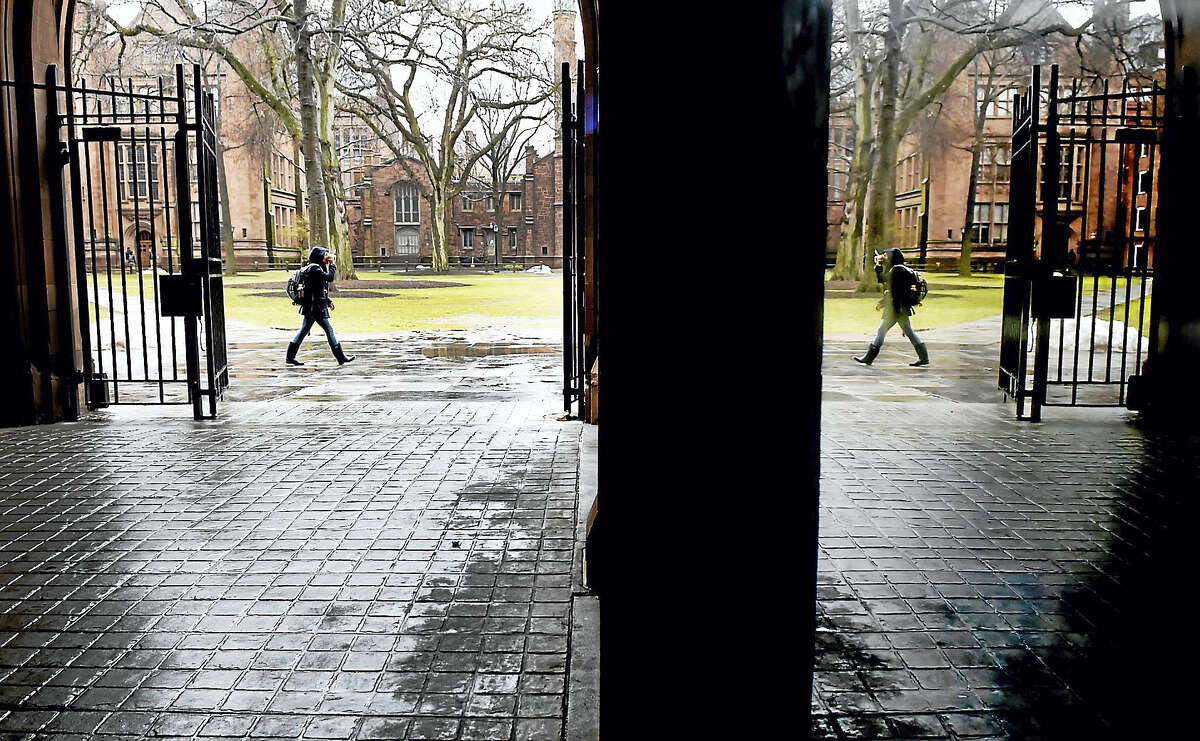 A passer-by on the Yale University's Old Campus is mirrored in a reflection on a display case inside Phelps Gate.