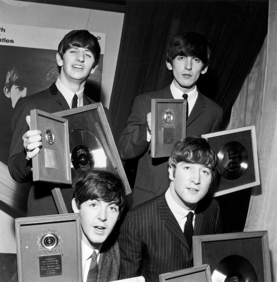 "The Beatles holding their silver LP and EP discs presented to them by EMI records in London to mark sales of records including the LP ""Please Please Me"" and ""Twist And Shout,"" the best-selling EP of all time. Clockwise from back left: Ringo Starr, George Harrison, John Lennon and Paul McCartney. Photo: Central Press — Getty Images   / Hulton Archive"