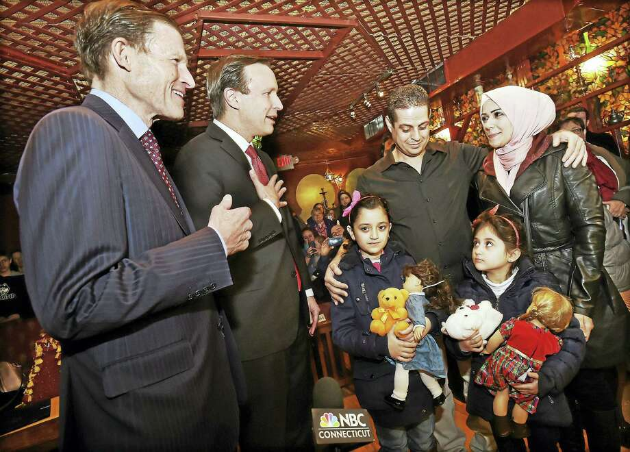 From left, U.S. Sens. Richard Blumenthal and Sen. Chris Murphy welcome Syrian refugees Fadi Kassar, his wife, Razan Ghandour, and their two young daughters, Hanan Kassar, 8, and Layan Kassar, 5, at the Olive Tree Mediterranean Deli in Milford Friday. Photo: Catherine Avalone — New Haven Register   / Catherine Avalone/New Haven Register