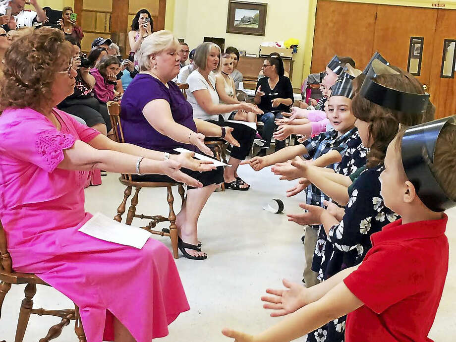 West Haven Green Nursery School Director Jean Palmer, far left, and teachers Lynda Bennett and AnnMarie Sullivan lead the school's last 16 graduates in a round of songs on Friday. Photo: Mark Zaretsky — New Haven Register