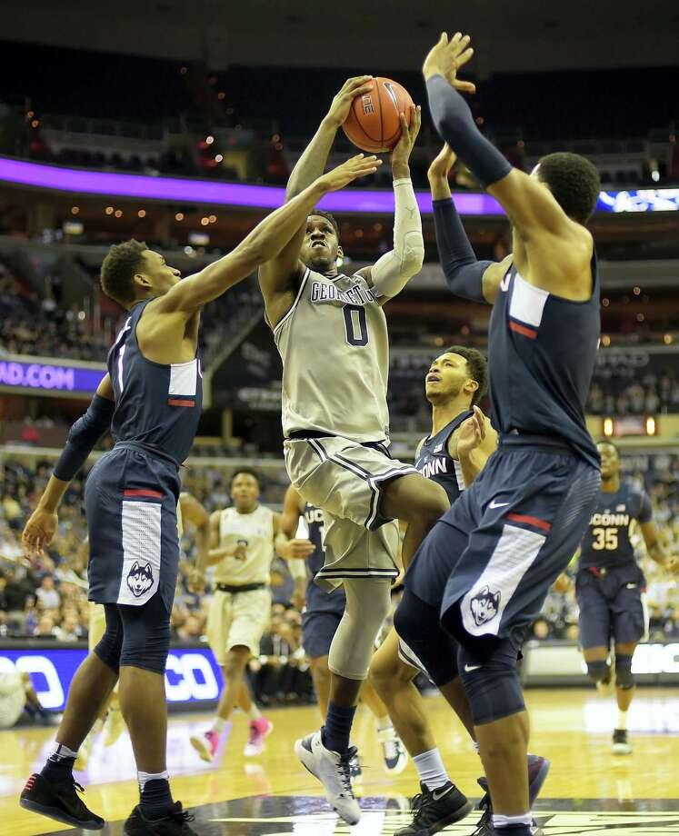 Georgetown's' L.J. Peak, center, drives through several UConn defenders during Saturday's game. Photo: John McDonnell — The Washington Post Via AP   / The Washington Post