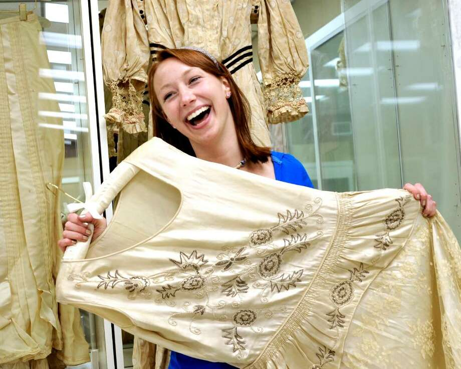 Meaghan Gorman, 21, holds a wedding dress from 1929 while installing an exhibit of historic wedding items at the Danbury Museum and Historical Society on Friday, May 28. 2010. Photo: Michael Duffy / The News-Times
