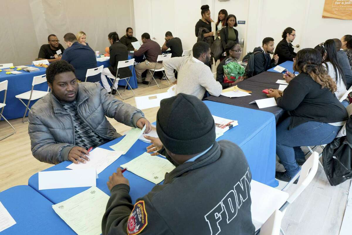 In this Nov. 15, 2016 photo, Kenneth Bennett, left, talks with a recruiter from the Fire Department City of New York during a job fair hosted by the Gregory Jackson Center for Brownsville, in the Brooklyn borough of New York. On May 4, 2017, the Labor Department reports on the number of people who applied for unemployment benefits a week earlier.