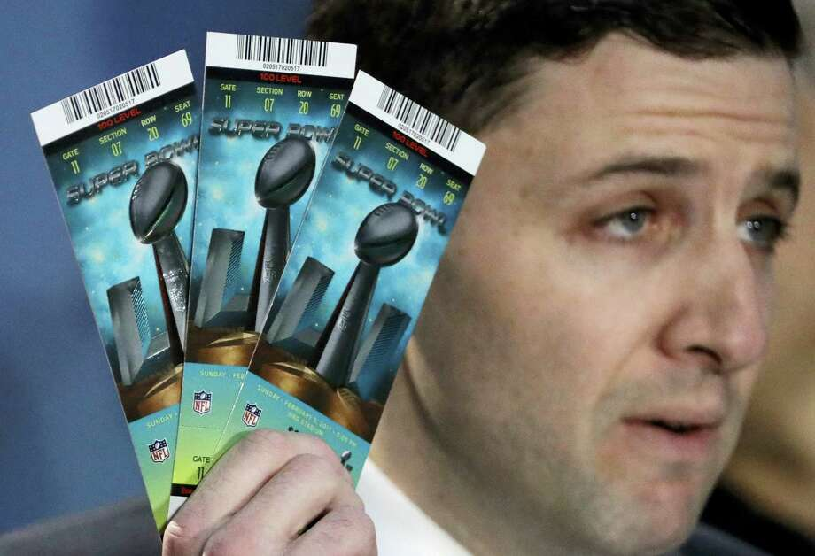 NFL Senior Counsel of Legal Affairs Michael Buchwald holds up Super Bowl 51 tickets as he explains the anti-counterfeit features of legitimate tickets. Photo: David J. Phillip — The Associated Press   / AP