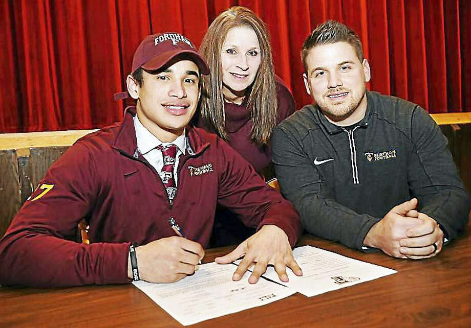 Sheehan senior running back Zach Davis signs a national letter of intent Wednesday at Mark T. Sheehan High School in Wallingford to play football at Fordham University this fall. Photo: Catherine Avalone — New Haven Register