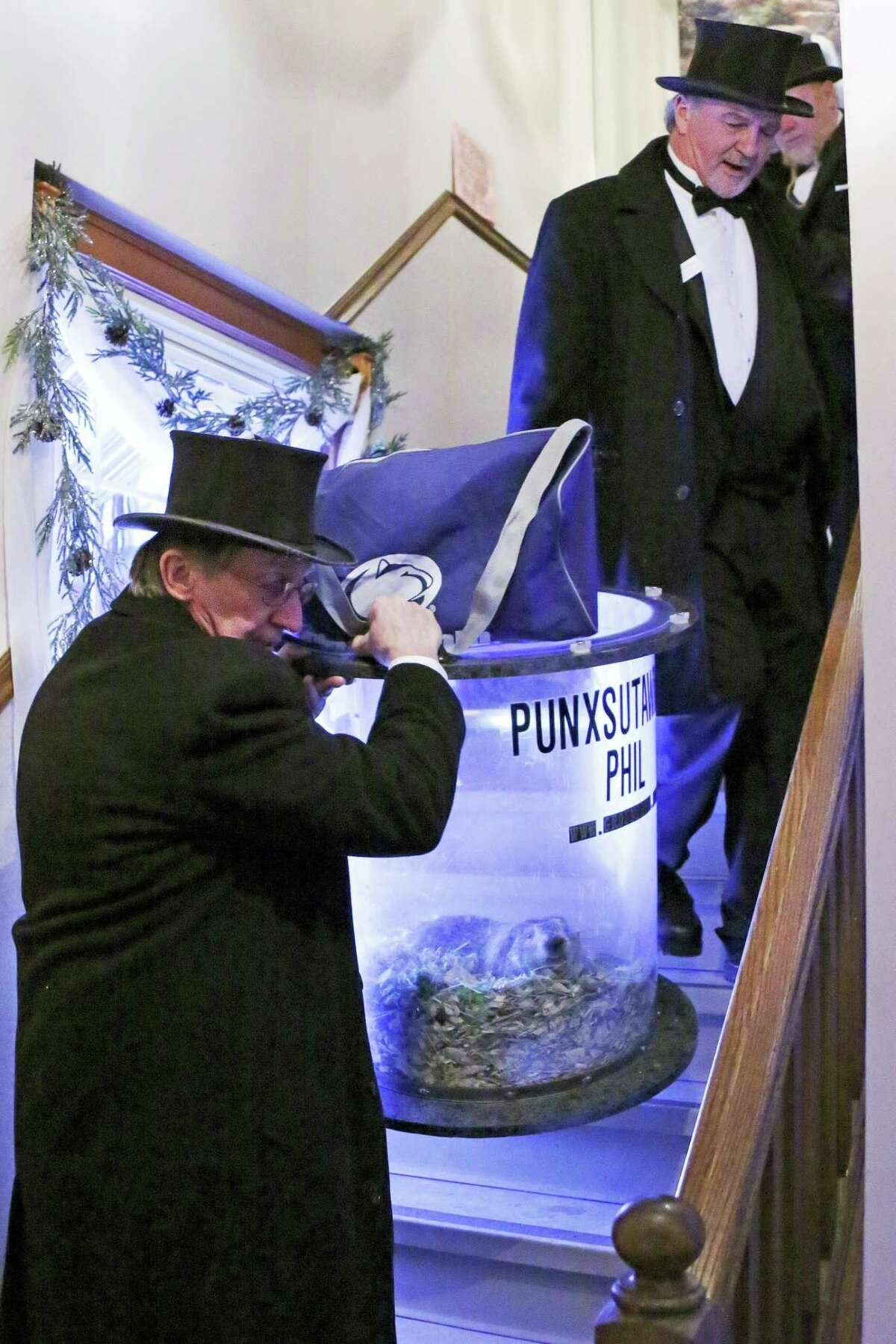 Groundhog Club handlers John Griffiths, top right and Ron Ploucha, left, carry Punxsutawney Phil, the weather prognosticating groundhog, down a flight of stairs after attending a function on Groundhog Day eve in Punxsutawney, Pa. on Feb. 1, 2017. The members of the Punxsutawney Groundhog Club's inner circle with make their trek to Gobber's Knob for the 131st time early Thursday morning.