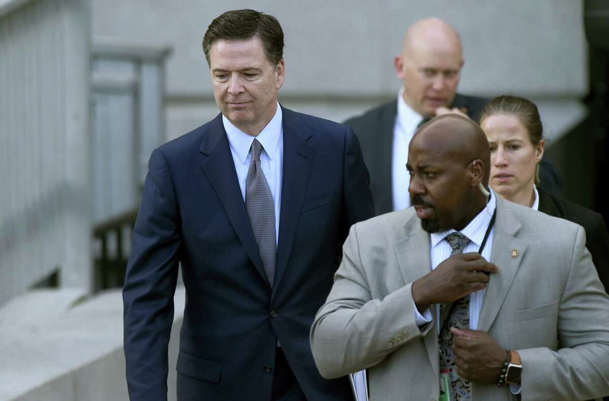 FBI Director James Comey, left, leaves the Eisenhower Executive Office Building on the White House complex in Washington.