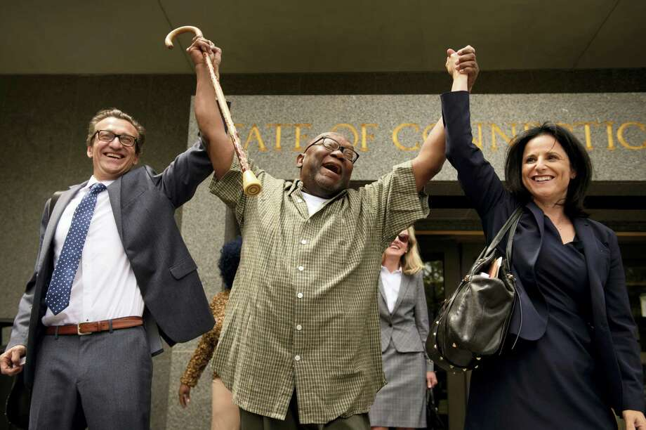 """Shouting """"Freedom,"""" Alfred Swinton, middle, walks out of Connecticut Supreme Court Thursday, June 8, 2017, in Hartford, Conn.,  with Innocence Project lawyers Chris Fabricant, left, and Vanessa Potkin after a Superior Court judge approved a new trial in his conviction in the 1991 murder of Carla Terry. After serving 18 years, Swinton, 68, was released on a promise to appear in court. Photo: Mark Mirko/Hartford Courant Via AP    / ©2017 The Hartford Courant"""