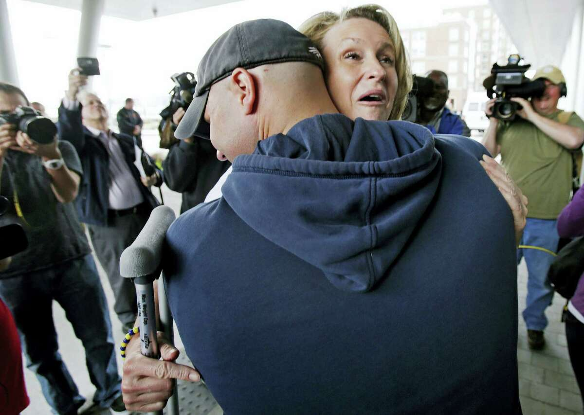 Boston Marathon bombing survivor Roseann Sdoia, from the North End neighborhood of Boston, is hugged and lifted off the ground by Boston firefighter Mike Meteria as she leaves Spaulding Rehabilitation Hospital in Boston in 2013.
