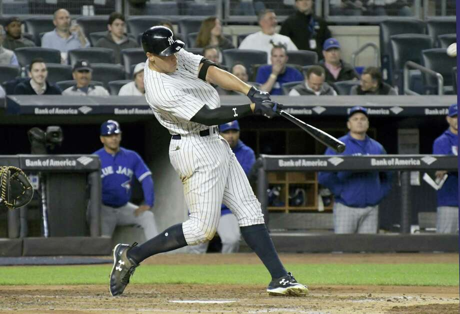 New York'S Aaron Judge hits a two-run home run during the third inning of the team's 8-6 win Wednesday night against the Toronto Blue Jays. It was Jude's major league-leading 13th homer of the season. Photo: BILL KOSTROUN — THE ASSOCIATED PRESS   / FR51951 AP