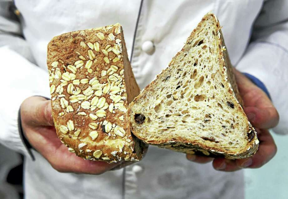 Andrea Corazzini, owner and general manager of Whole G Bakery, holds a cross section of the MuesliBrot. Photo: Arnold Gold — New Haven Register