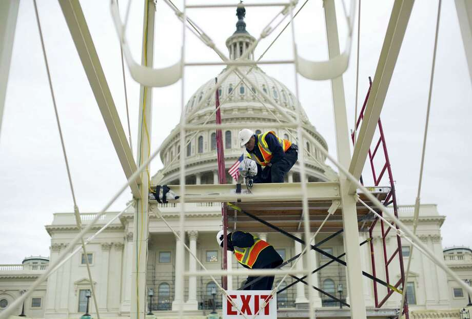 Construction continues on the Inaugural platform in preparation for the Inauguration and swearing-in ceremonies for President-elect Donald Trump, on the Capitol steps in Washington. Trump's Presidential Inaugural Committee has raised a record $90 million-plus in private donations, far more than President Barack Obama's two inaugural committees. They collected $55 million in 2009 and $43 million in 2013, and had some left over on the first go-round. But while Trump has raised more money for his inauguration than any president in history, he's aiming to do less with it. Photo: Pablo Martinez Monsivais — AP File Photo   / Associated Press WashDC