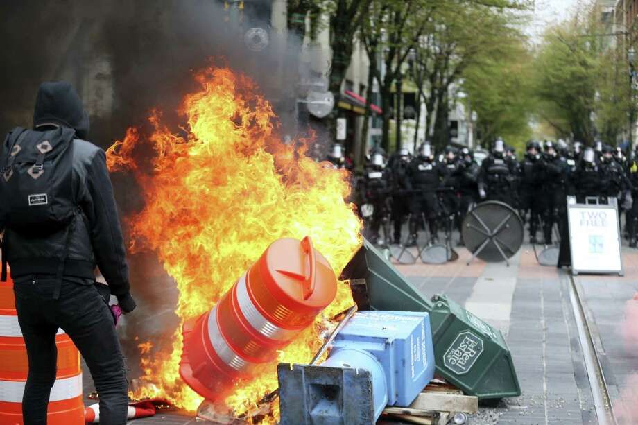 Police try to disperse people participating in a May Day rally in downtown Portland, Ore., Monday. Police in Portland said the permit obtained for the May Day rally and march there was canceled as some marchers began throwing projectiles at officers. Photo: Dave Killen — The Oregonian Via AP   / The Oregonian