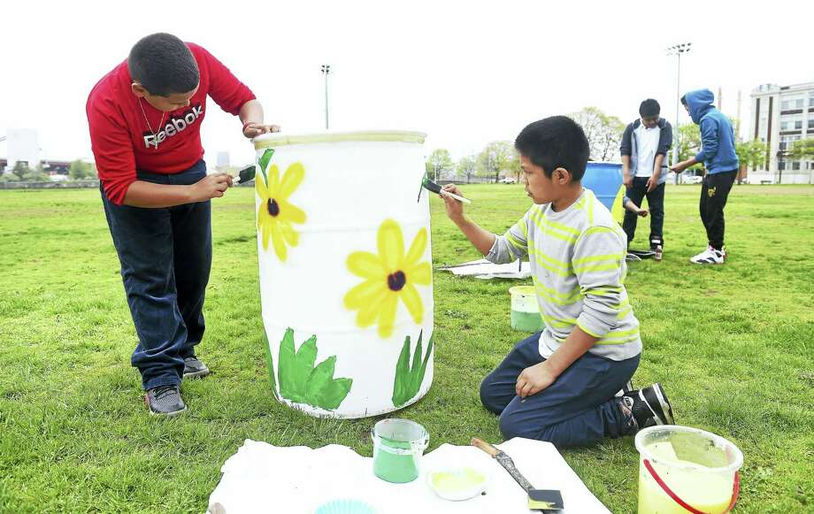 Fair Haven School ESL students Henry David, left, 11, and Bilbai Oliver, 12, paint a trash can at Criscuolo Park in New Haven. Photo: Arnold Gold — New Haven Register