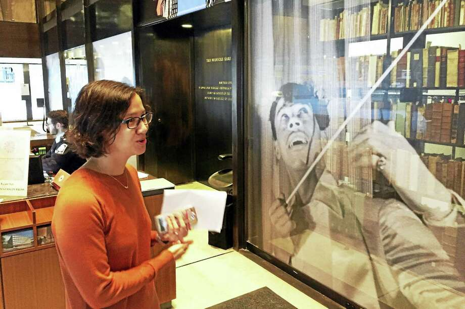 Curator Melissa Barton talks to a visitor in the Beinecke lobby near the stacks tower and an image of Cab Calloway. Photo: Joe Amarante — Register