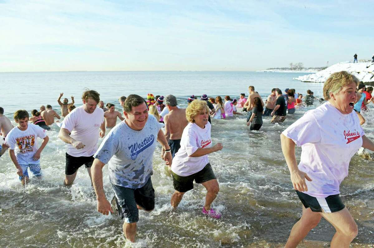 An estimated 200 participants — including Mayor Ed O'Brien, Westies T-shirt, and his son, David, red-and-white T-shirt — dash in and out of 41-degree water in Long Island Sound during the 16th annual Icy Plunge for the Cure benefit Feb. 6 at Savin Rock Beach.