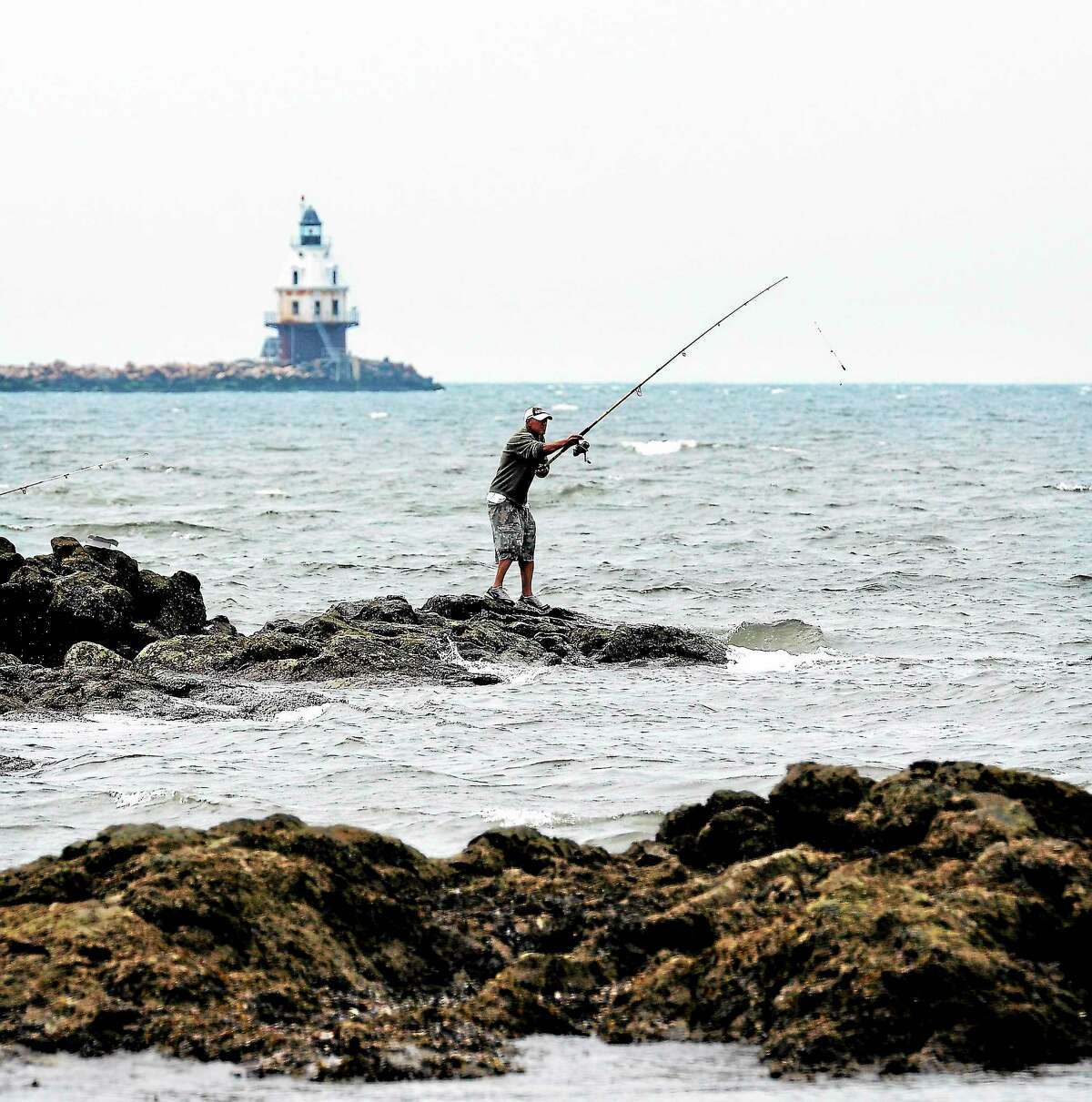 Casting a line off the rocks at Lighthouse Point Park in New Haven.