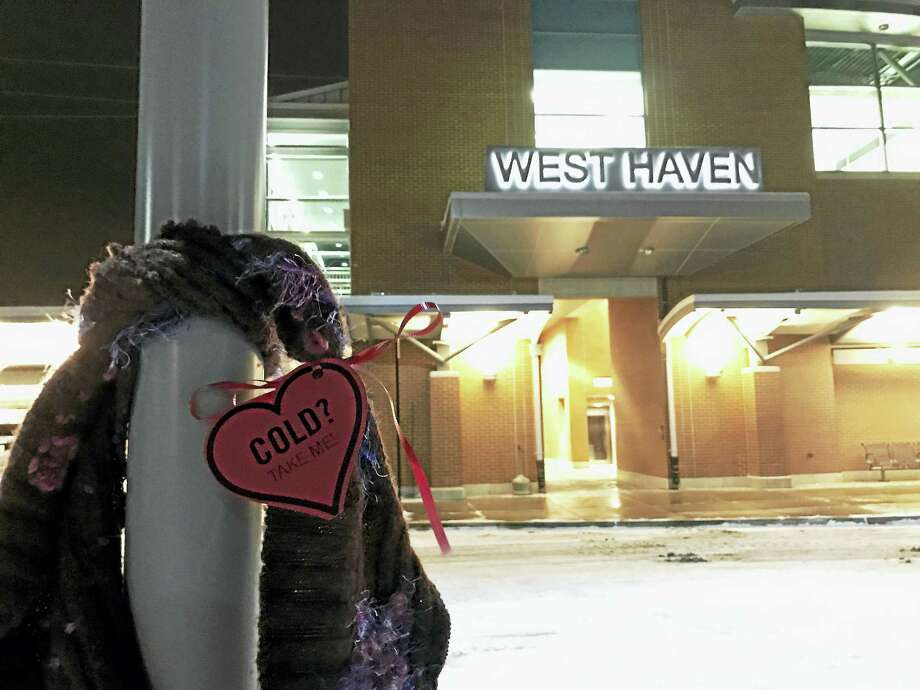 As United Way of Greater New Haven kicked off Neighbor to Neighbor campaign, on Tuesday night people set out with scarves and wrapped them around poles and posts in the area. Photo: Contributed Photo
