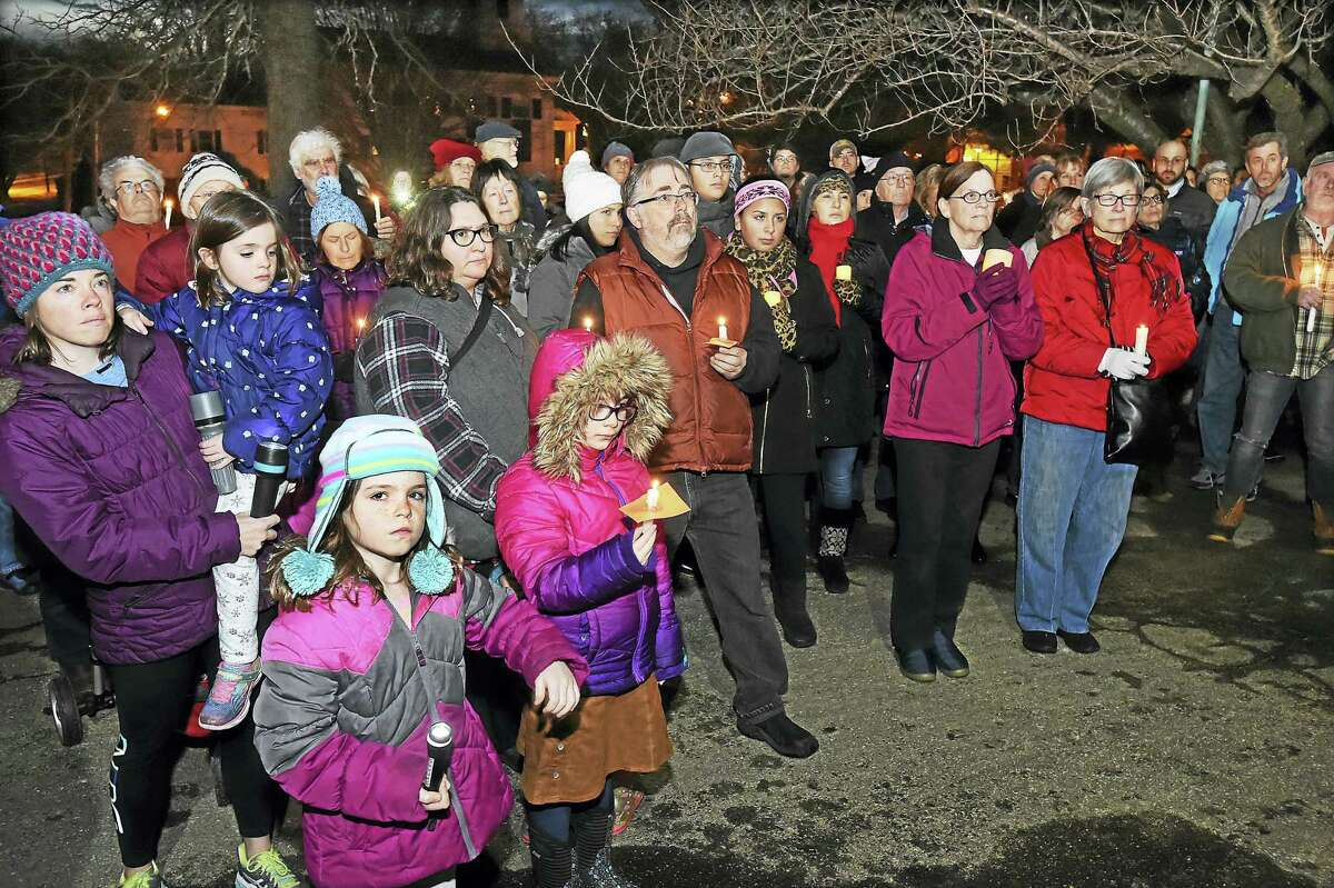 Area residents gather at a candlelight vigil sponsored by the Branford Refugee Welcoming Committee at First Congregational Church on the Branford Green Wednesday.
