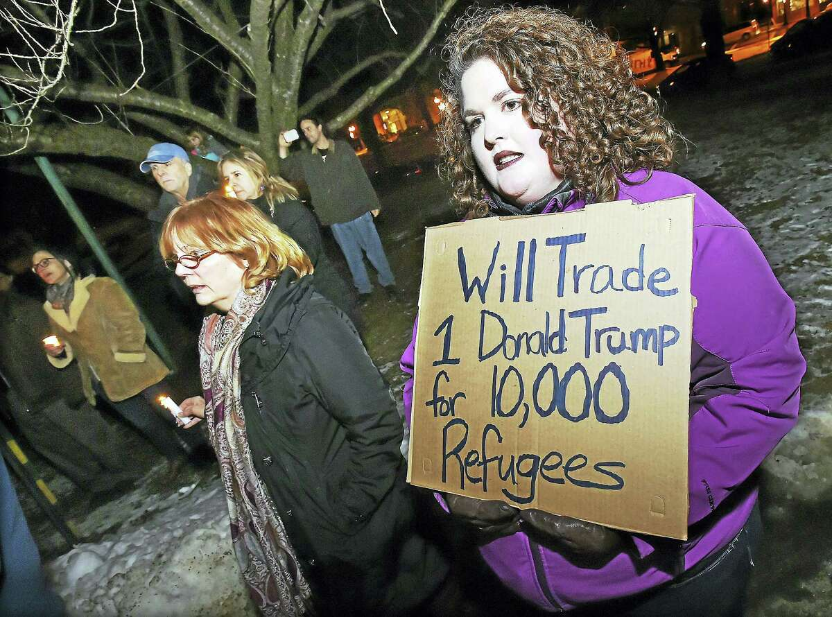 """New Haven residents Sara Hungerford, holding sign, and her mother, Carol Labore, sing """"We Shall Overcome"""" at a candlelight vigil at First Congregational Church on the Branford Green Wednesday."""