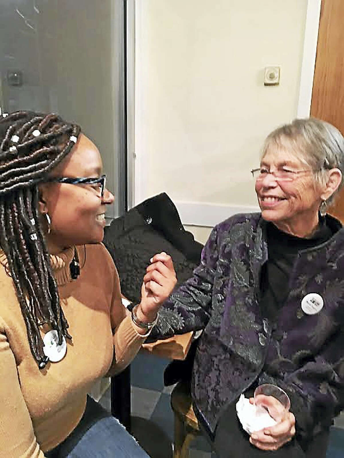 Tyra Pendergrass, left, and Marie Tupper, both members of the New Haven Land Trust board, get to know each other better at a celebration Wednesday marking the partnership with Schooner Inc.