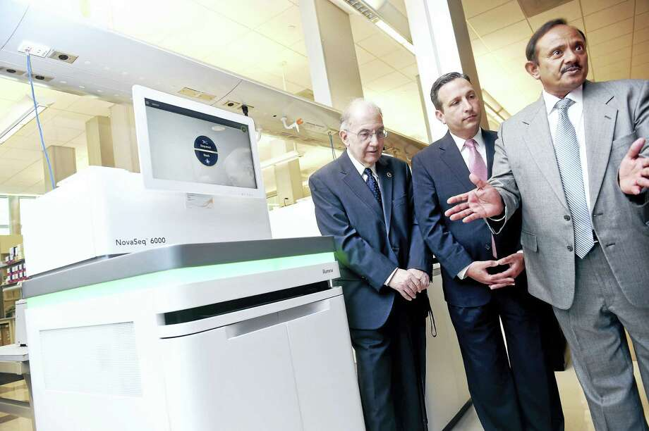 From left, state Senate President Martin Looney, D-New Haven, and state Senate Majority Leader Bob Duff, D-Norwalk, listen to Shrikant Mane, executive director of the Yale Center for Genome Analysis, talk about DNA sequencing next to one of two NovaSeq 6000 Sequencing Systems at the Yale Center for Genome Analysis in West Haven Monday. Photo: Arnold Gold — New Haven Register