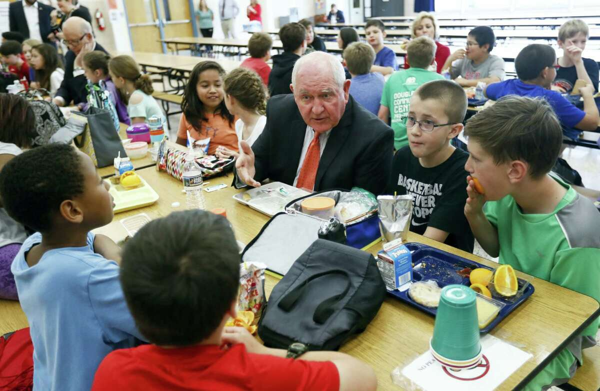 Agriculture Secretary Sonny Perdue has lunch with students in the cafeteria at Catoctin Elementary School in Leesburg, Va., Monday, after he unveiled a new rule on school lunches as the Trump administration and other Republicans press for flexibility after eight years of the Obama's emphasis on health eating.