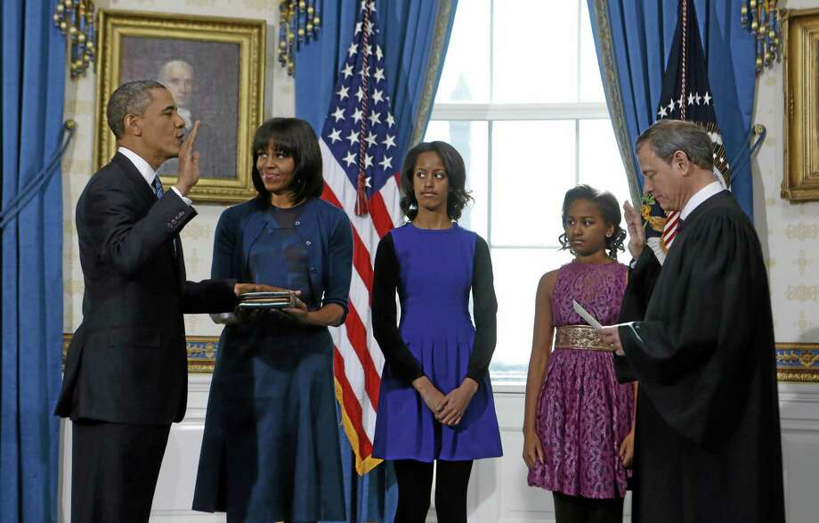 President Barack Obama is officially sworn-in by Chief Justice John Roberts in the Blue Room of the White House during the 57th Presidential Inauguration in Washington, Sunday, Jan. 20, 2013. Next to Obama are first lady Michelle Obama, holding the Robinson Family Bible, and daughters Malia and Sasha. Photo: AP Photo/Larry Downing, Pool / Pool Reuters