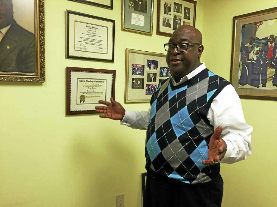 The Rev. Boise Kimber speaks about the photos in his office at First Calvary Baptist Church onWednesday in New Haven. Photo: Esteban L. Hernandez — New Haven Register