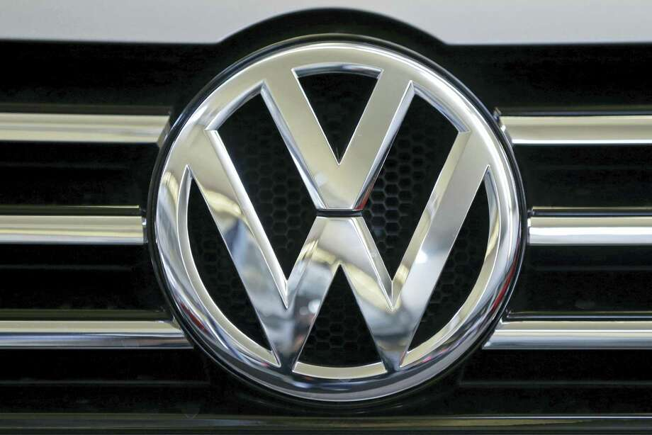 The Volkswagen logo is seen on the grill of a Volkswagen on display in Pittsburgh in 2013. The imminent criminal plea deal between Volkswagen and U.S. prosecutors in an emissions-cheating scandal could be bad news for one group of people: VW employees who had a role in the deceit or subsequent cover-up. VW on Tuesday, Jan. 10, 2017, disclosed that it is in advanced talks to settle the criminal case by pleading guilty to unspecified charges and paying $4.3 billion in criminal and civil fines, a sum far larger than any recent case involving the auto industry. Photo: Gene J. Puskar — AP File Photo / Copyright 2017 The Associated Press. All rights reserved.