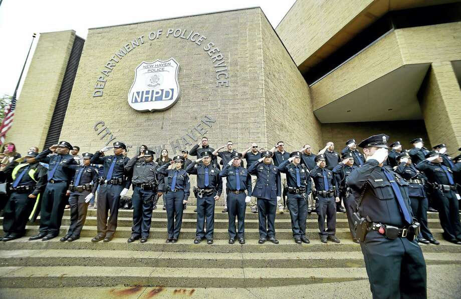 New Haven police salute as the funeral procession of Officer Edward Douglas passes the New Haven Police Department on Union Street in New Haven Monday. Photo: Arnold Gold — New Haven Register