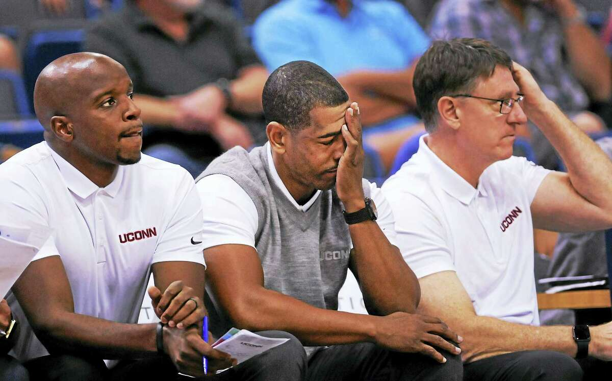Assistant coach Dwayne Killings, left, and associate head coach Glen Miller, right, look on as Connecticut's head coach Kevin Ollie, center, reacts to his team's performance early in the second half of an exhibition game against New Haven earlier this year in Hartford.