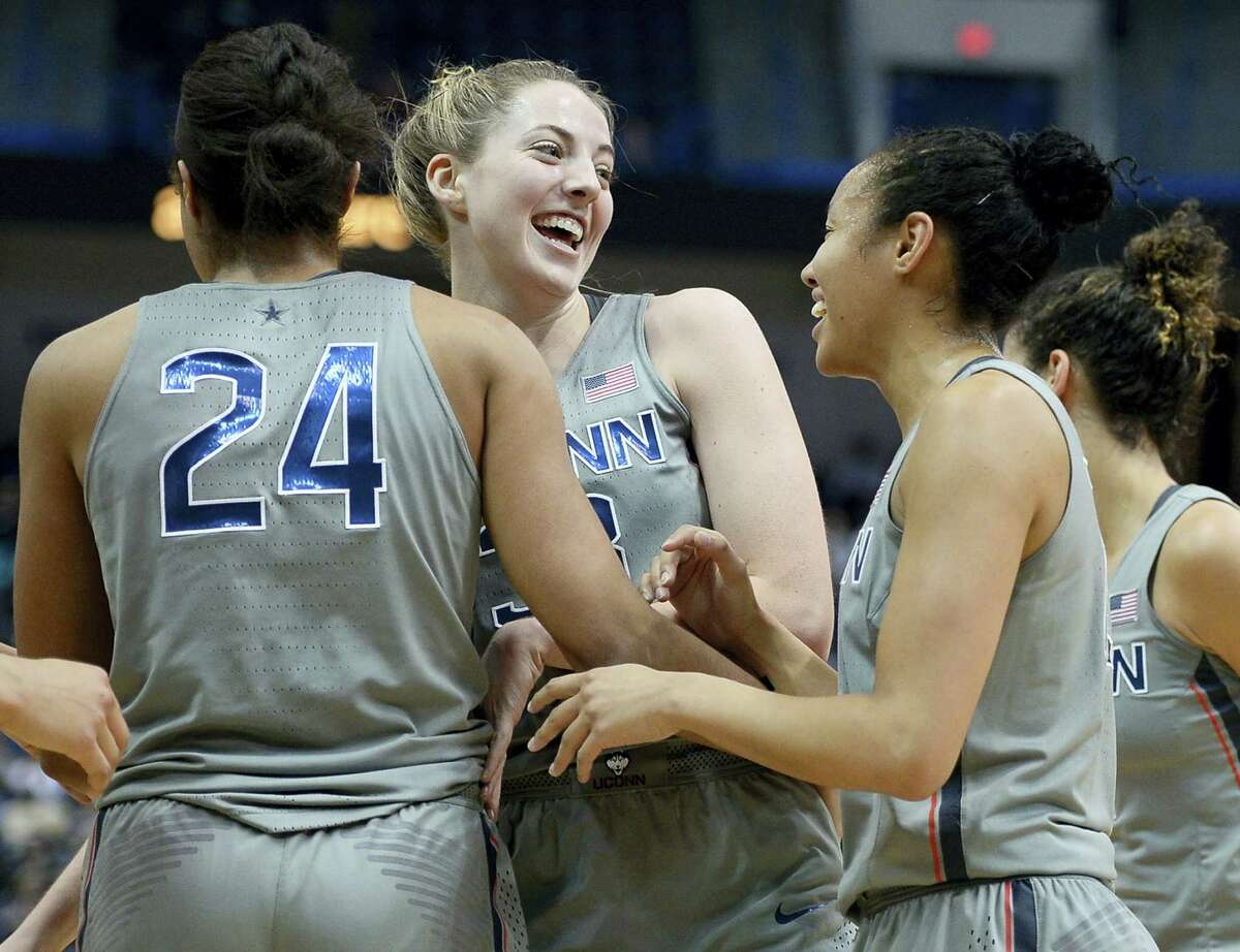 UConn's Katie Lou Samuelson, center, celebrates with teammates Napheesa Collier, left, and Saniya Chong, right, in the first half of an NCAA college basketball game against South Florida Tuesday in Hartford. UConn beta South Florida 102-37 for its 90th straight victory, tying its own record.