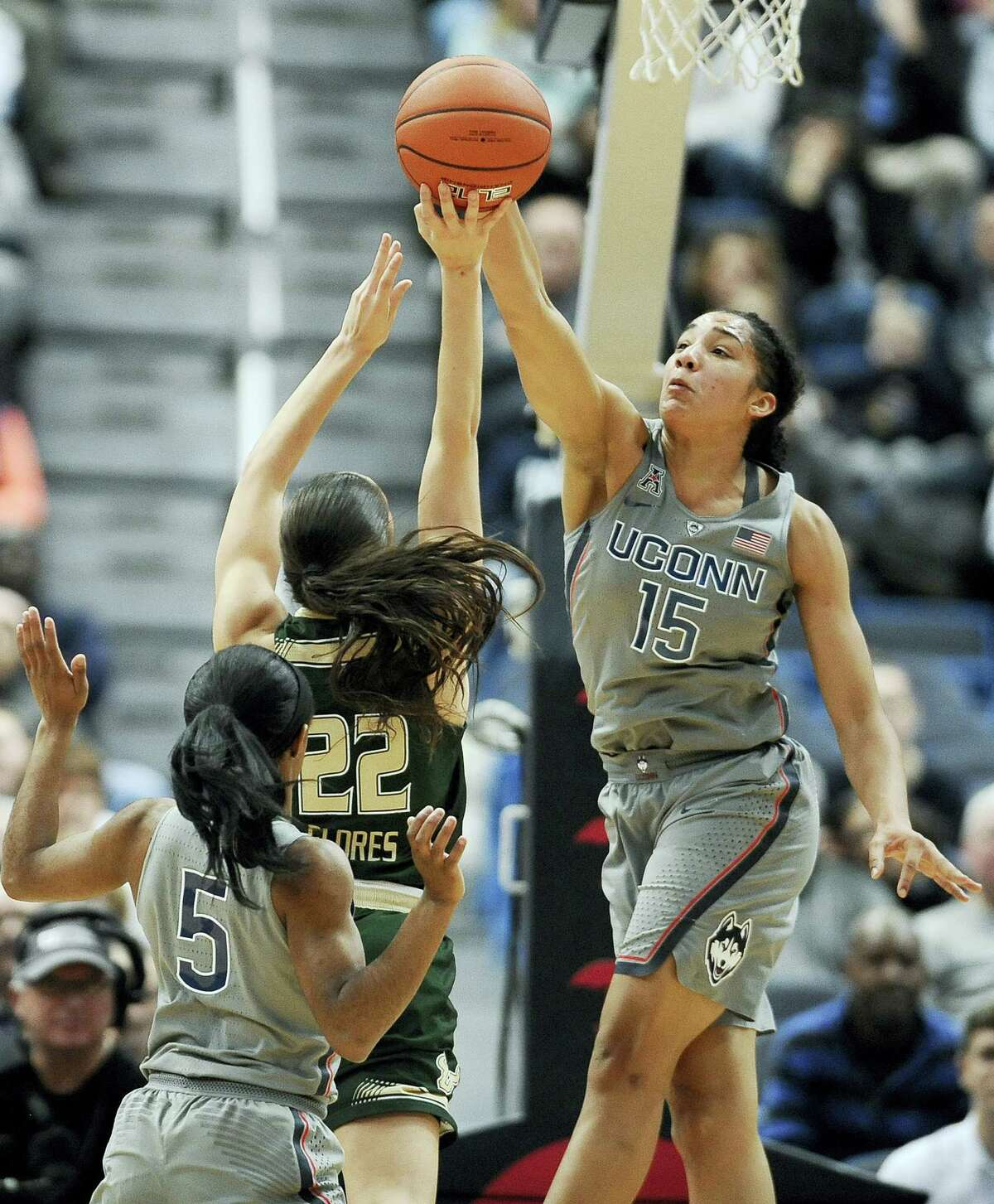 UConn's Gabby Williams blocks a shot attempt by South Florida's Laia Flores, center, as UConn's Crystal Dangerfield left, defends, in the first half of the Huskies' 90the consecutive victory.