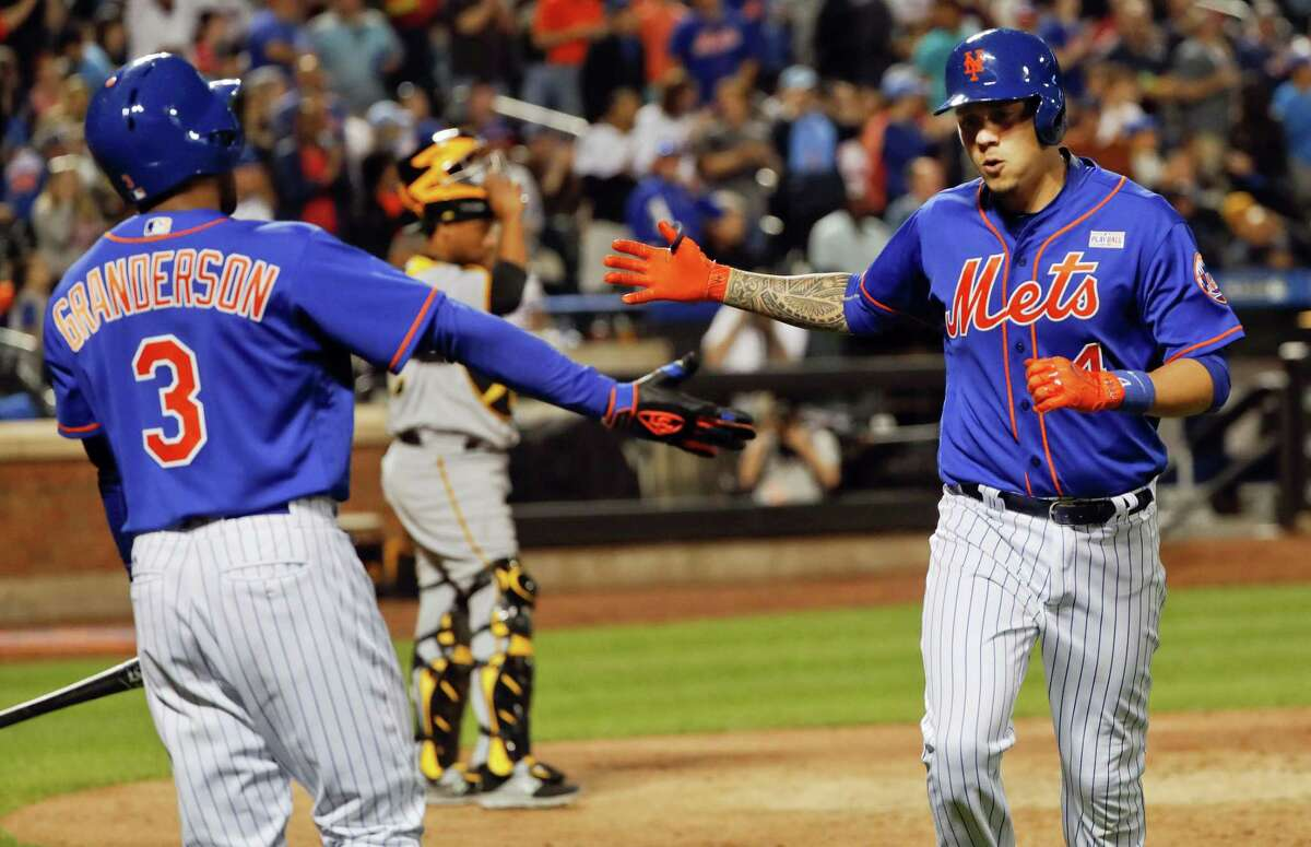 New York Mets' Wilmer Flores, right, is congratulated by Curtis Granderson (3) after hitting a solo home run against the Pittsburgh Pirates during the fourth inning of a baseball game, Saturday, June 3, 2017, in New York. (AP Photo/Julie Jacobson)